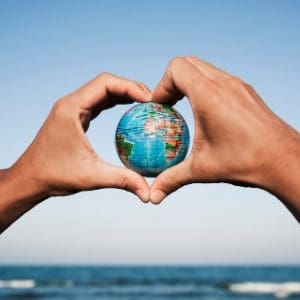 hands holding small globe with ocean in background