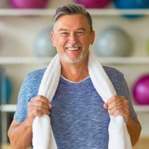 man with towel around neck in gym with exercise balls on shelf behind him