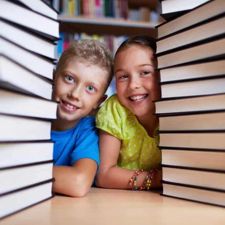 boy and girl with stacks of books