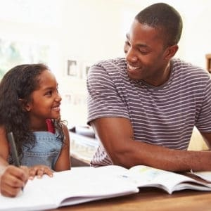 photo of dad and daughter working on homework together